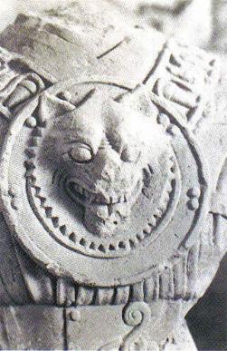 Escultura de piedra que representa un guerrero protegido con un disco-coraza que en el centro lleva esculpido un lobo